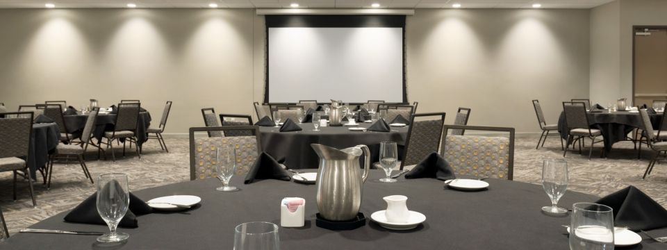 Meeting space with round banquet tables and projector screen