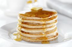 Tall stack of pancakes with butter and syrup