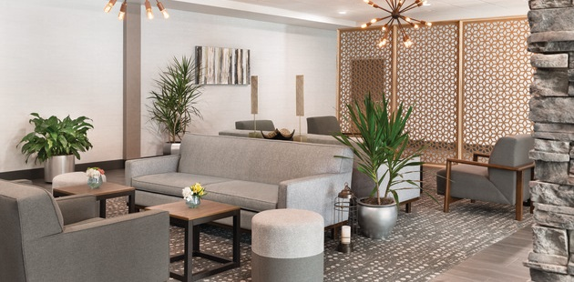 Hotel lobby with gray furniture, modern light fixtures and potted plants