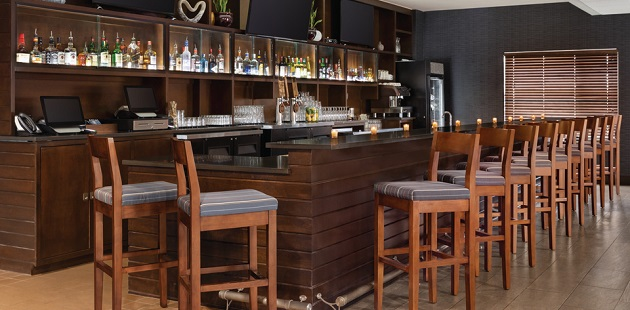Fully stocked bar featuring dark wooden accents, flat-screen TVs and high-top seating