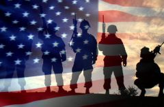 Silhouetted US soldiers behind American flag