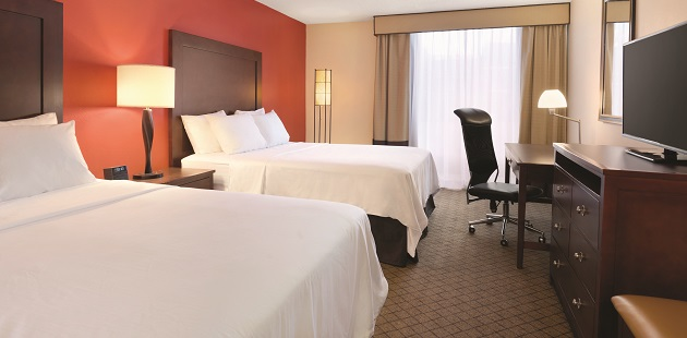 Hotel room with two double beds and a desk