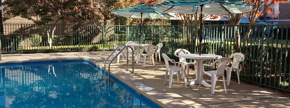 Outdoor pool with shaded areas and seating