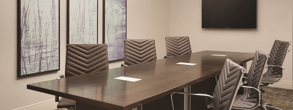 Boardroom setup with rectangular table and brown cushioned chairs
