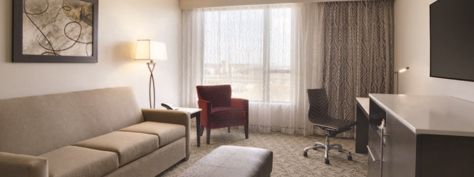 Suite's living room with sofa, ottoman and flat-screen TV