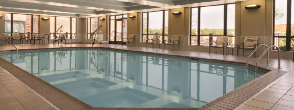 Indoor pool with plenty of windows and seating