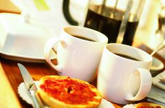 Two cups of coffee and a bagel spread with jam