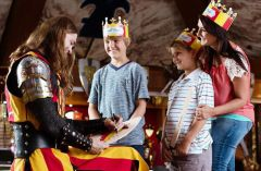Medieval Times knight signing merchandise for a family