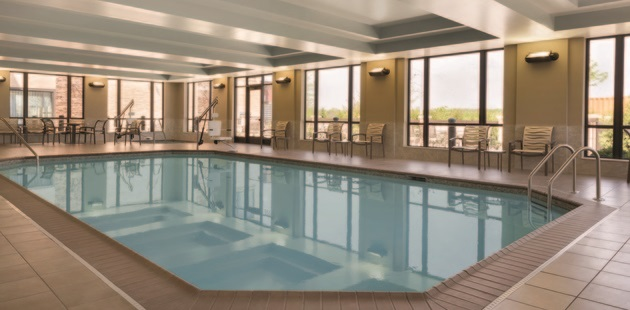 Indoor pool with plenty of seating and floor-to-ceiling windows