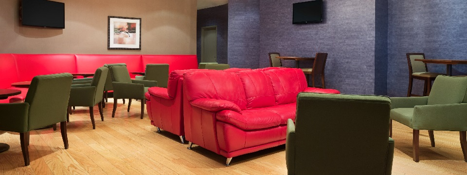31Hundred lounge area with wall-mounted TVs and red sofas