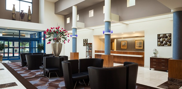 Hotel lobby with plush seating and a large flower arrangement