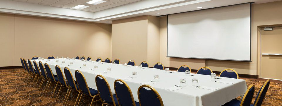 Hotel meeting room with long conference table and projector