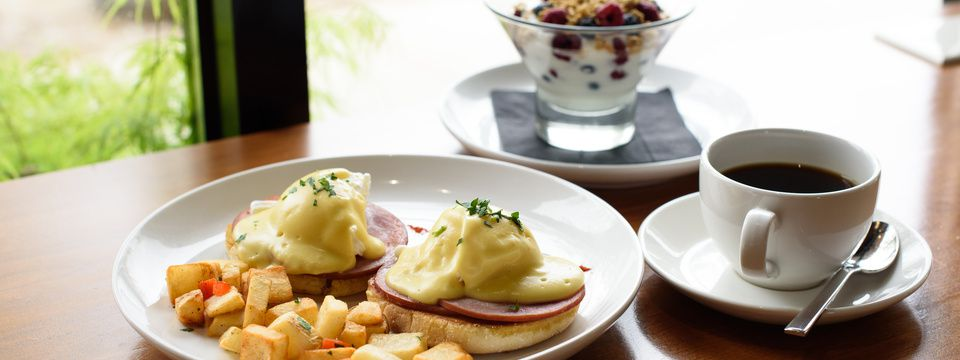 Eggs Benedict served with potatoes, a cup of coffee, and a fruit and yogurt parfait
