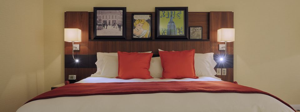 Guest room featuring a king bed with artistic images along the headboard