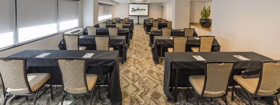 Two rows of rectangular tables covered with black linens