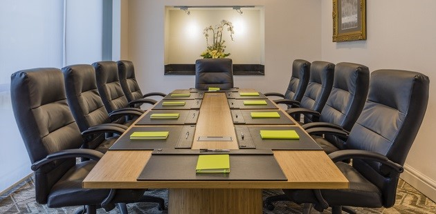 Boardroom table set with green notebooks