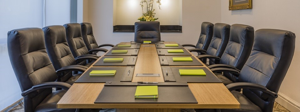 Boardroom set with green notebooks and pens
