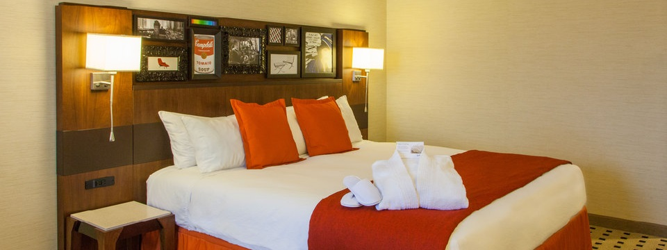 King bed with unique headboard, side table and orange accent pillows