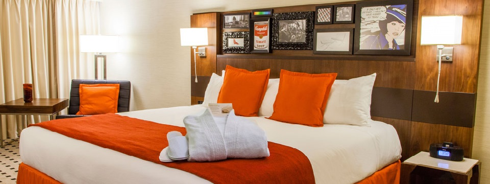 King bed with artistic headboard and orange accent pillows
