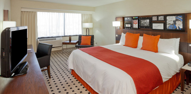 King bed with orange accents and flat-screen TV in hotel room
