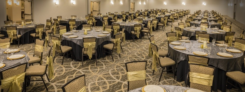 Rows of round tables with gold accent bows in ballroom