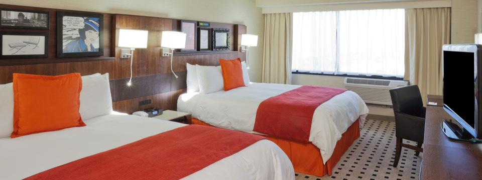 Two queen beds with orange accents and flat-screen TV