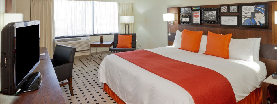 King bed with orange accents, flat-screen TV and armchair in hotel room
