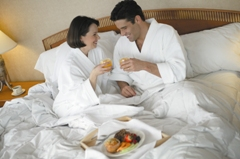 Man and a woman in white bathrobes sharing breakfast in bed