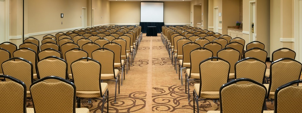 Hotel meeting space set up theater style with a projector screen