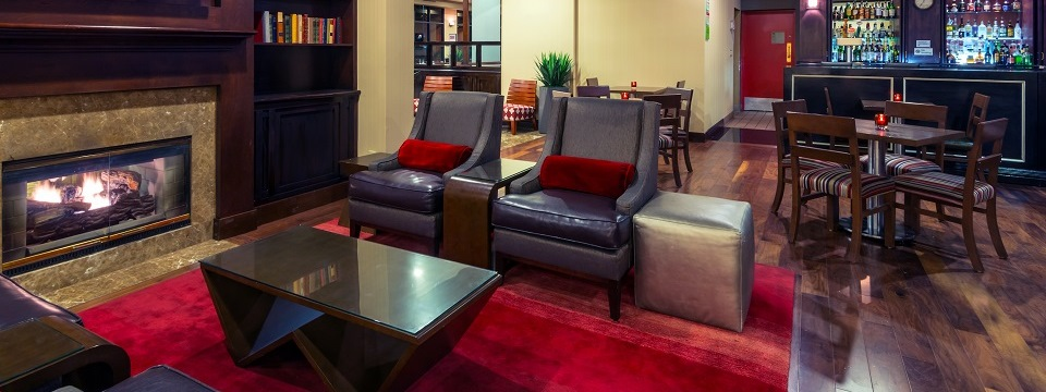 Lounge with a fireplace, leather seats and a fully stocked bar