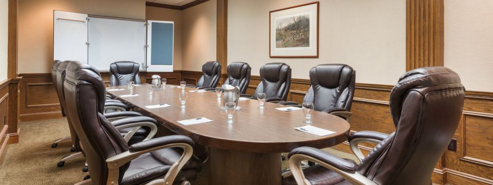 Boardroom featuring a conference table and plush leather chairs