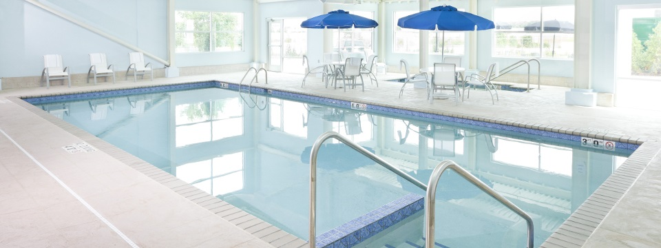 Indoor pool with seating and umbrellas