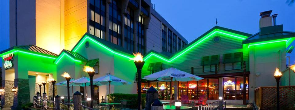 Exterior of hotel and restaurant lit with green lights