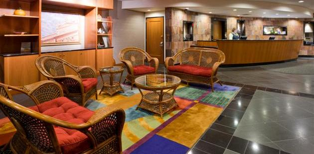 Welcoming lobby with wicker furniture and a colorful rug