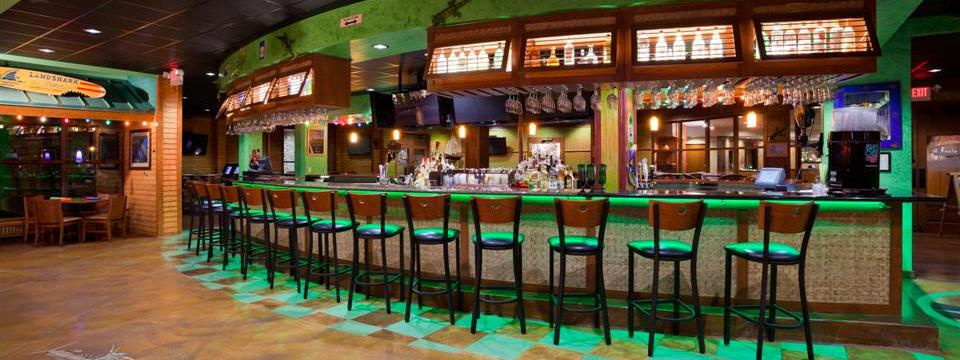 Long bar lit up with green lights and surrounded by stools
