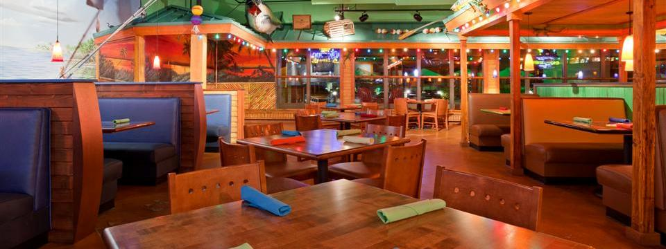 Tables and booths with colorful napkins and lights at Jimmy's Island Grill