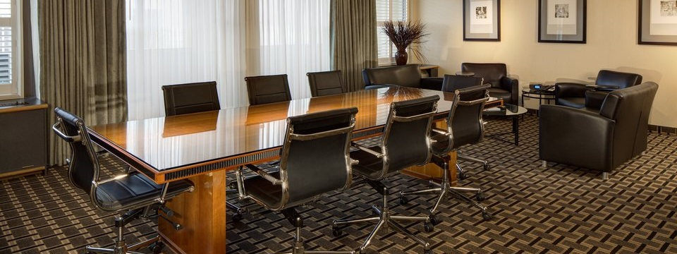 Boardroom with tables, chairs and a small sitting area with arm chairs