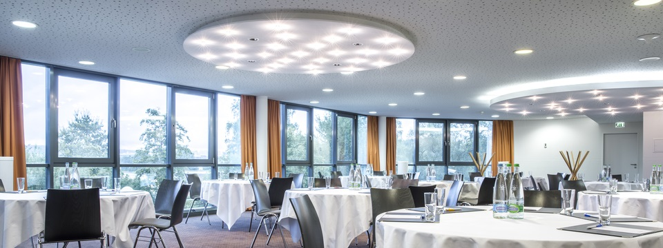 Meeting room with round tables and abundant windows