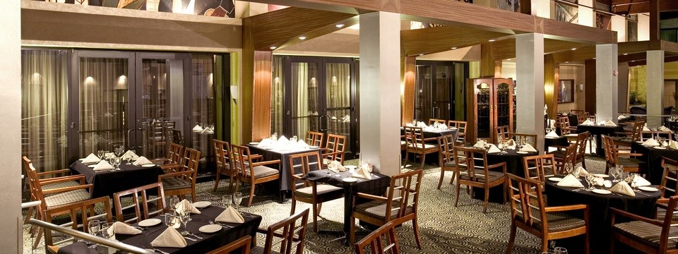 Hotel restaurant with ample seating, white pillars and wooden accents