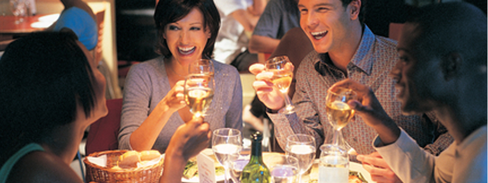 People laughing over dinner and drinks