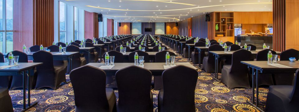 Spacious meeting hall with a patterned carpet and rows of tables and chairs